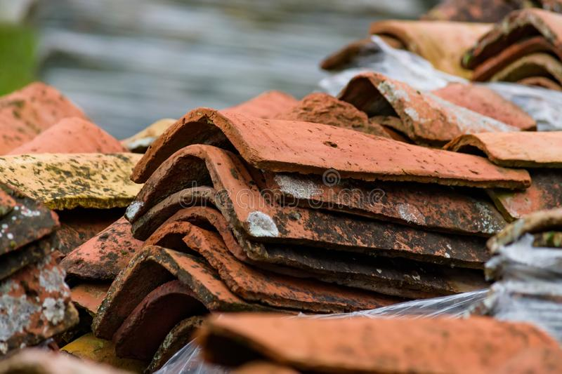 Stacked weathered red roof tiles on ground stock photo
