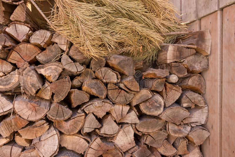 Stacked wood logs with dry pine tree branch against wooden panels. Chopped firewood. Woodpile concept. stock photography
