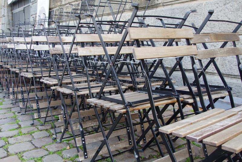 Stacked wooden chairs and tables on the empty street in the early morning stock photography