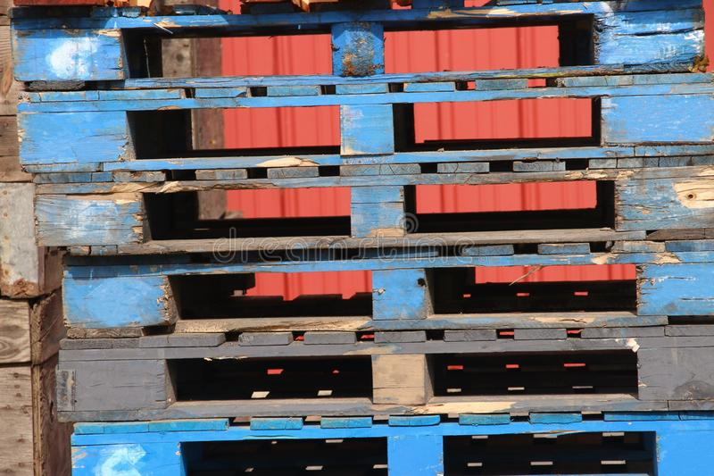 Weathered blue wooden pallets with an orange background. stock image
