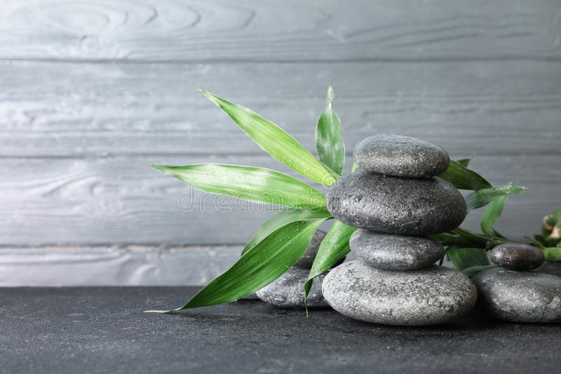 Stacked zen stones and bamboo leaves on table against wooden background. Space for text royalty free stock photography