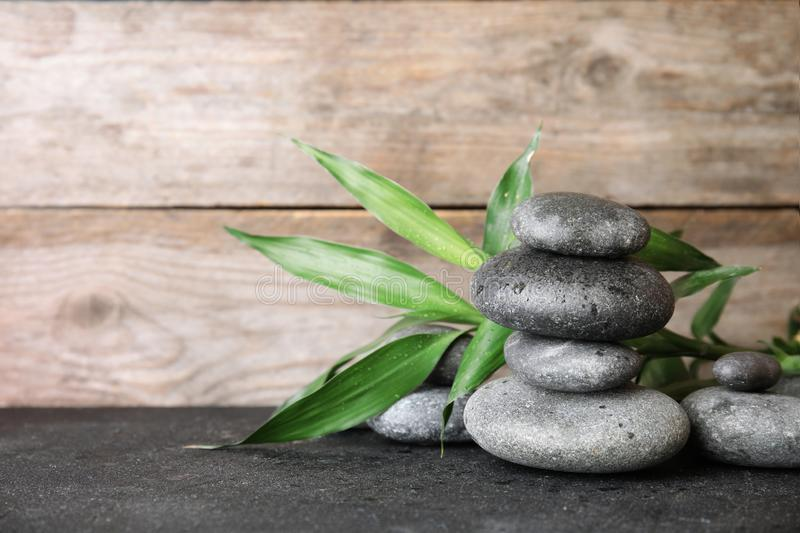 Stacked zen stones and bamboo leaves on table against wooden background. Space for text royalty free stock photos