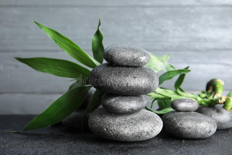Stacked zen stones and bamboo leaves on table. Against wooden background royalty free stock images