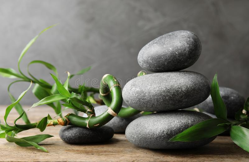 Stacked zen stones and bamboo on table against grey background. Space for text royalty free stock image