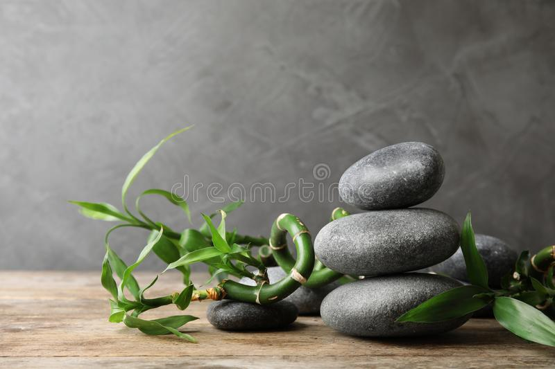 Stacked zen stones and bamboo on table against grey. Space for text. Stacked zen stones and bamboo on table against grey background. Space for text royalty free stock photography