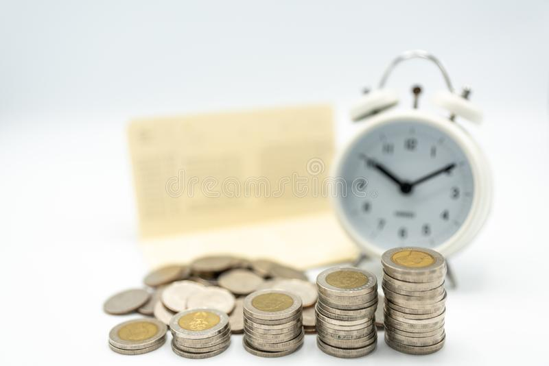 Stacking coins arranged as growth graph with soft focus of alarm clock and bookbank stock images