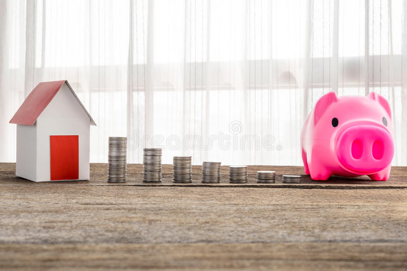 Stacking coins and home model for saving with growing money to r stock image