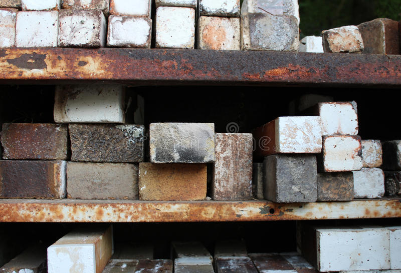 Stacks of ceramic kiln bricks on rusted metal shelves. Weathered old ceramic pottery kiln fire bricks, some with a crazed white salt glaze finish, stacked on royalty free stock images