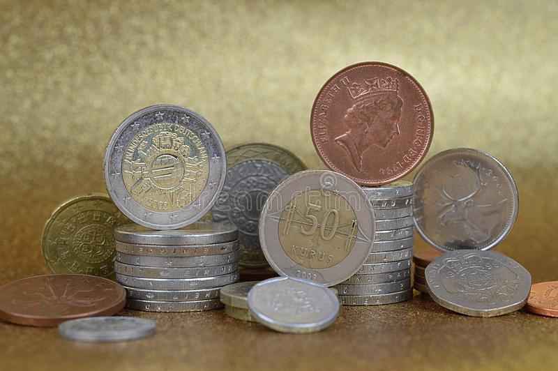 Stacks of coins from different nations. With Euros and Cents in front of golden background stock photos