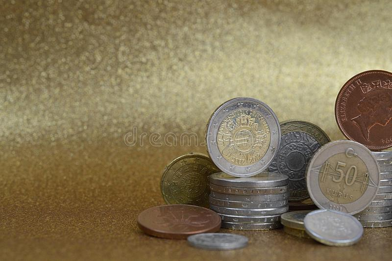 Stacks of coins from different nations with space. Stacks of coins from different nations with Euros and Cents in front of golden background with copy space to stock photos