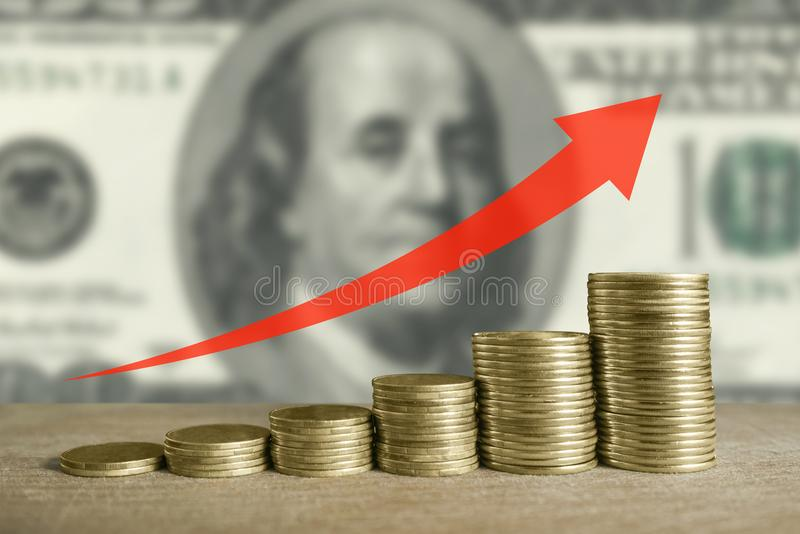 Stacks of coins on dollars as background and red arrow up royalty free stock photos