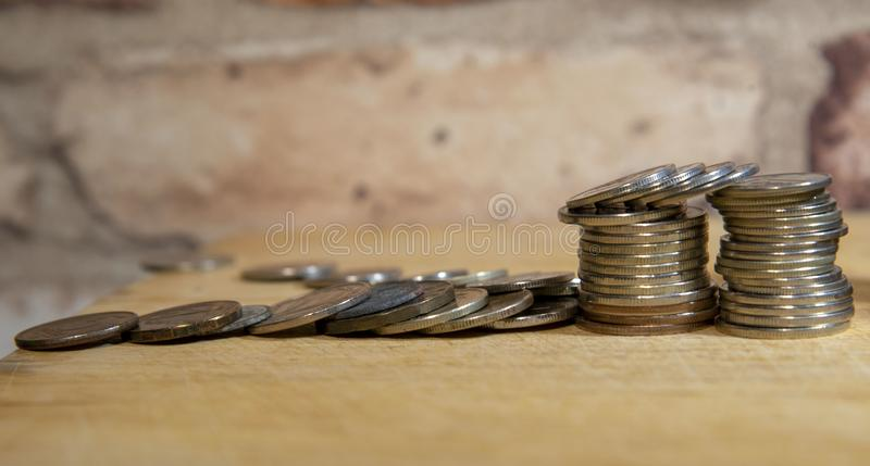 Stacks of coins and a vintage brick wall stock photography