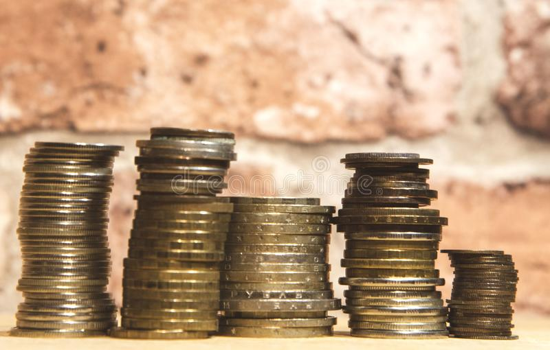 Stacks of coins and a vintage brick wall royalty free stock photography