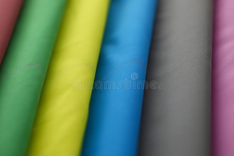 Stacks of colorful clothes. Close-up of many material tender silk on market of different colors green, yellow, blue, grey and burgundy. Fabric swatches stacked royalty free stock image