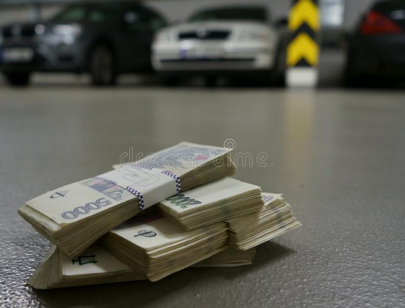 Stacks of money on a floor in an office garage with cars in the background stock image