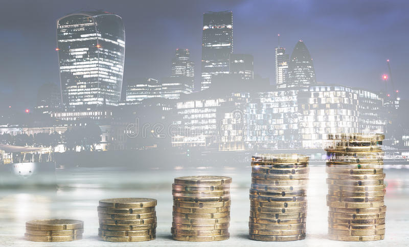 Stacks of growth money coins, double exposure with London finance skyline background stock photography