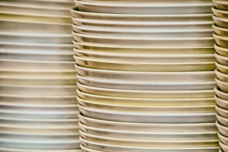 Stacks of many white plates on a wire rack shelf in a commercial stock photos