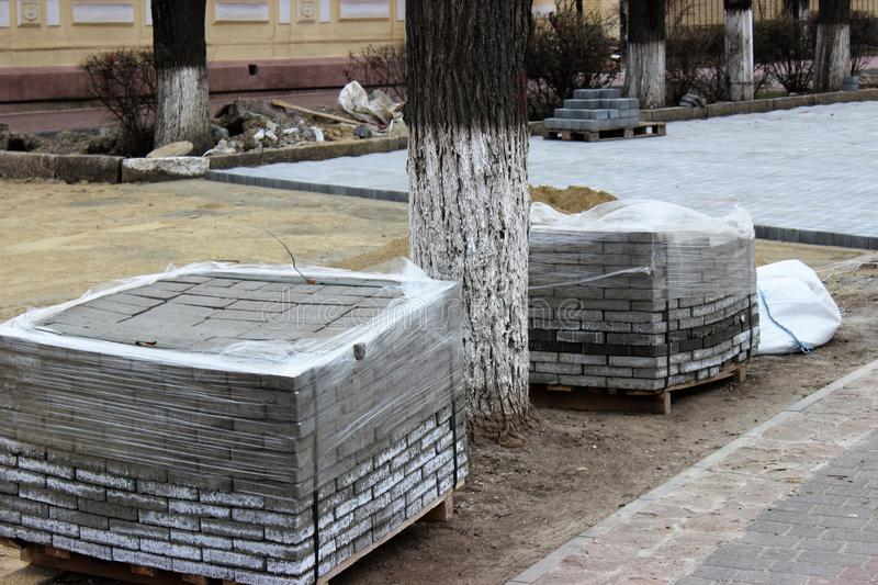 Stacks of modern tiles before laying instead of the old street pavers royalty free stock image