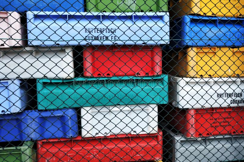 Stacks of multicolored plastic boxes used by fishermen at the Baltic Sea stacked behined wire mesh fence at fish factory stock photo