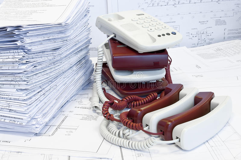 Stacks of phones and drawings royalty free stock image