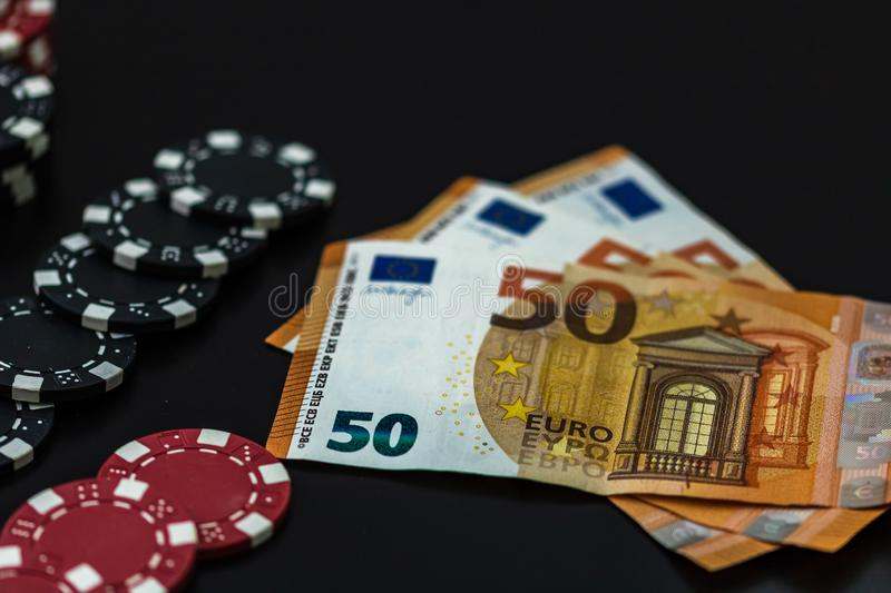 Stacks of poker chips and EURO bills on black background. Poker concept, chips and money stock image