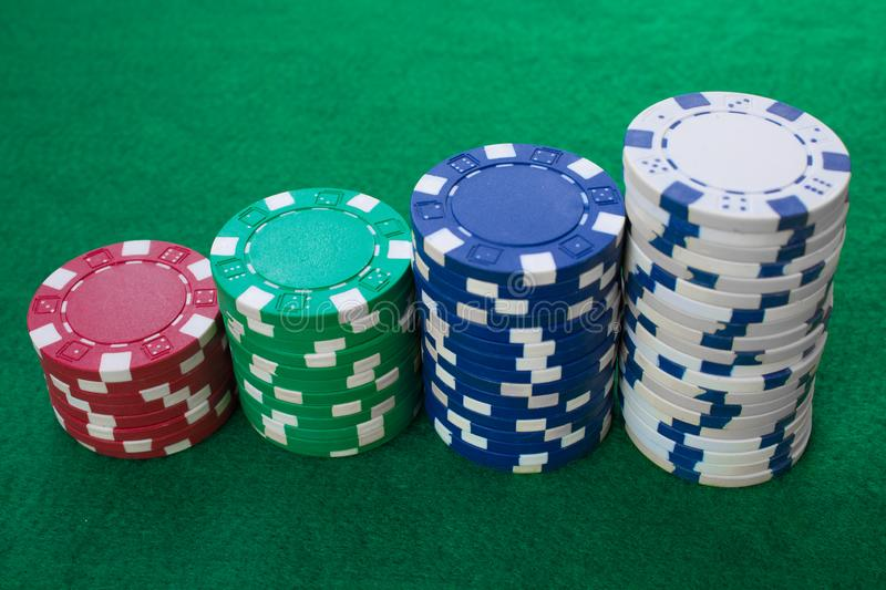Stacks of poker chips including red, white, green and blue on a green background. Perspective view stock photos