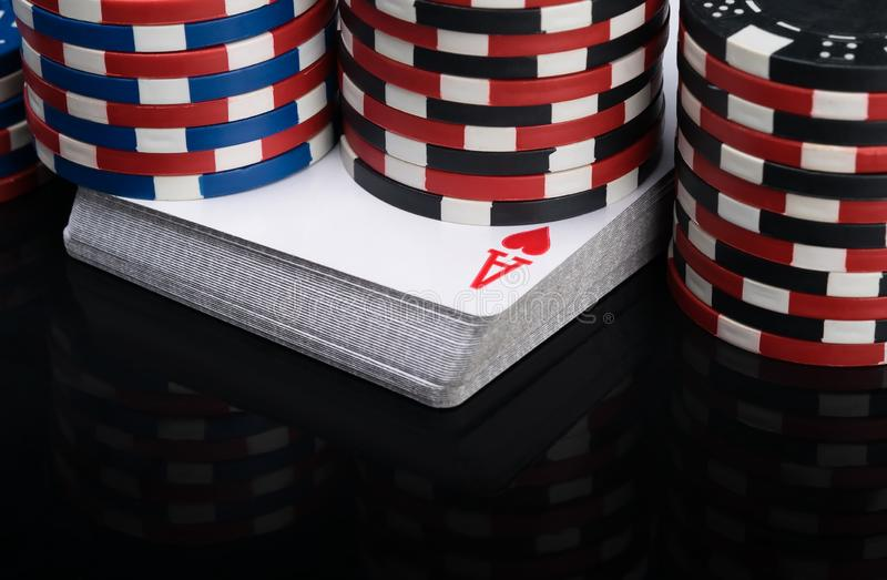 Stacks of poker chips stand on a deck of playing cards and are reflected in a glossy black table close-up royalty free stock images
