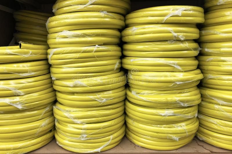 Stacks of rolls yellow pvc plastic pipe on the counter in the store stock images