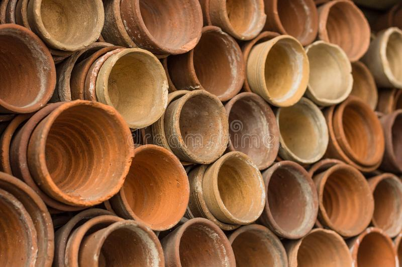 Stacks of terracotta flowerpots in a gardeners potting shed at botanical garden. Many stacked ceramic pots for plants. Old ceramic royalty free stock images