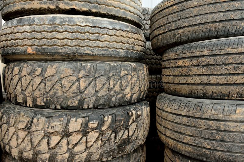 Stacks of used worn and muddy black rubber tires royalty free stock image