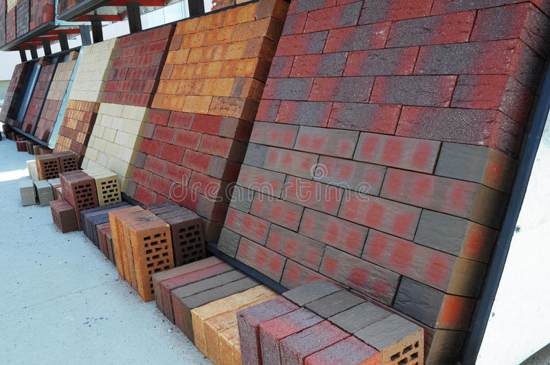 Stacks of various and for sale. Building colorful construction materials, colored concrete pavers (paving stone). Or patio blocks organized on pallets for sale royalty free stock image