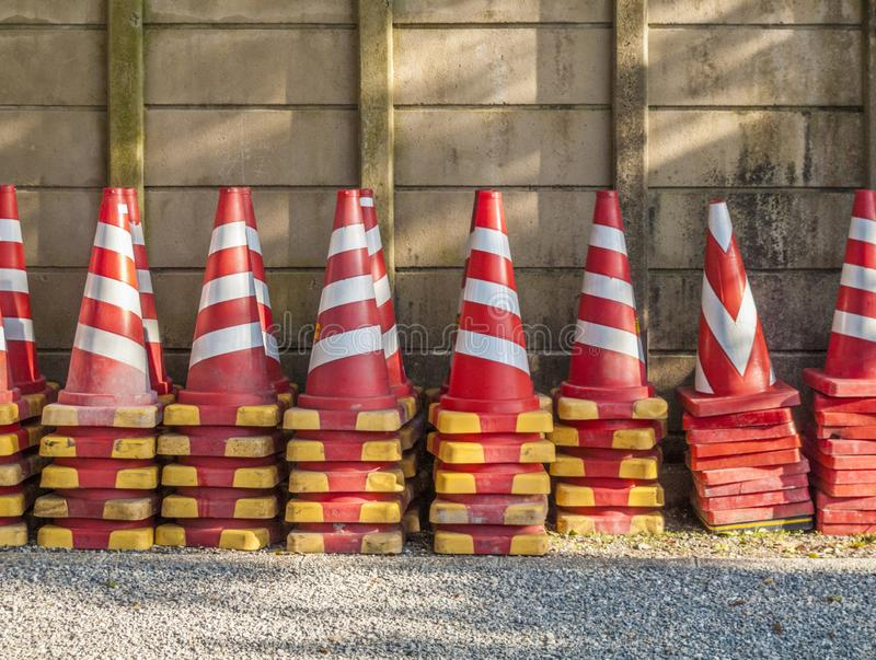 Stacks of witches hats lined up against a wall. Stacks of striped witches hats lined up against a wall stock photo