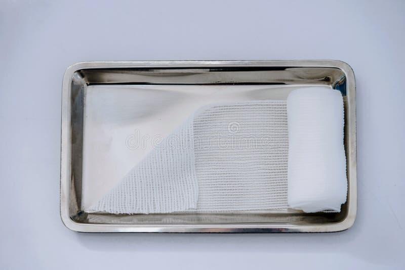 Stacza się gazę lub cienieje bandaż na medycznej tacy na białym bac fotografia stock