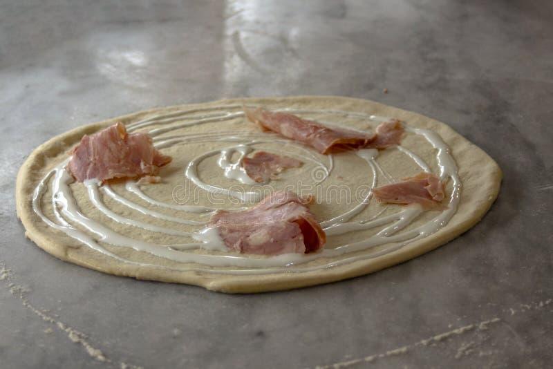 Staczający się pizzy ciasto z uwędzonym kurczakiem polędwicowym i kremowym - proces przygotowanie obrazy royalty free