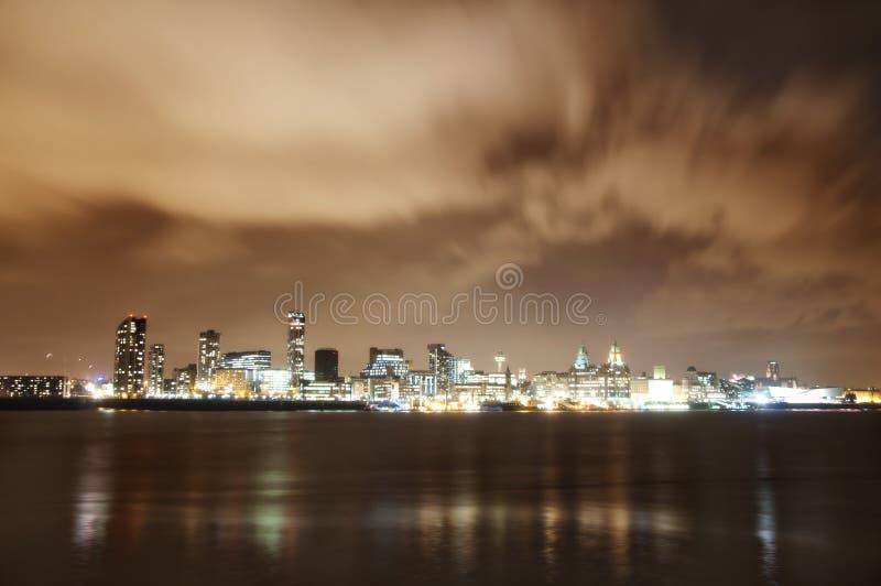 Stad av Liverpool, England, på natten och floden Mersey royaltyfri bild