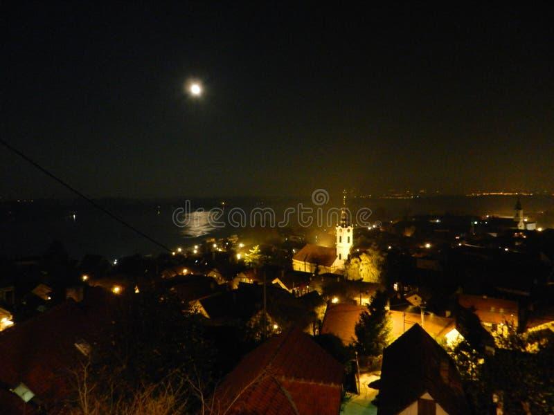 Stad av Zemun på natten, fullmåne royaltyfri bild