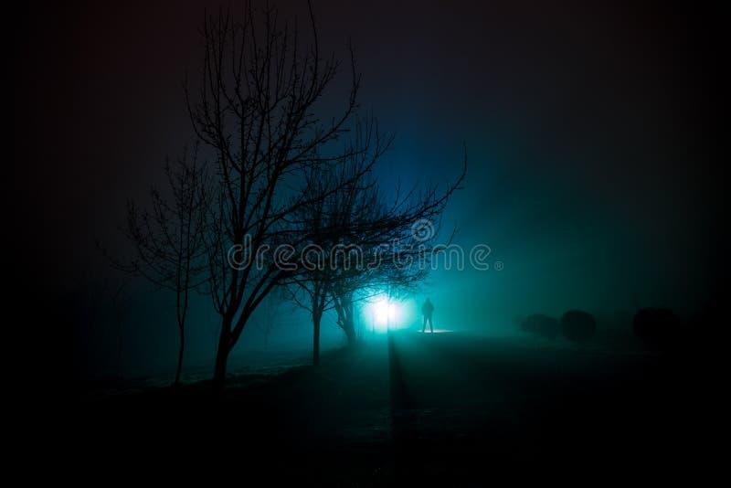 Stad bij nacht in dichte mist Mystiek landschaps surreal lichten met de griezelige mens Het het lopen man silhouet in nachtmist b royalty-vrije stock fotografie