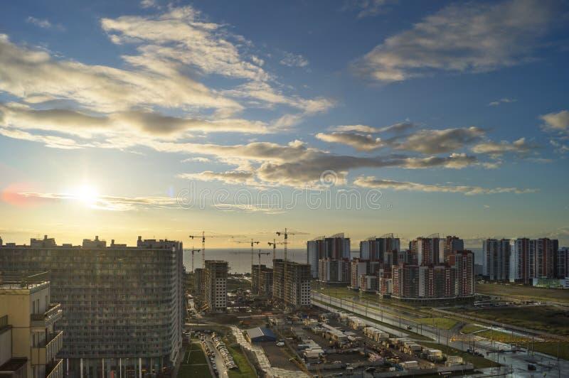 Stad bij zonsondergang De kust van de metropool in de stralen van de avondzon stock foto's