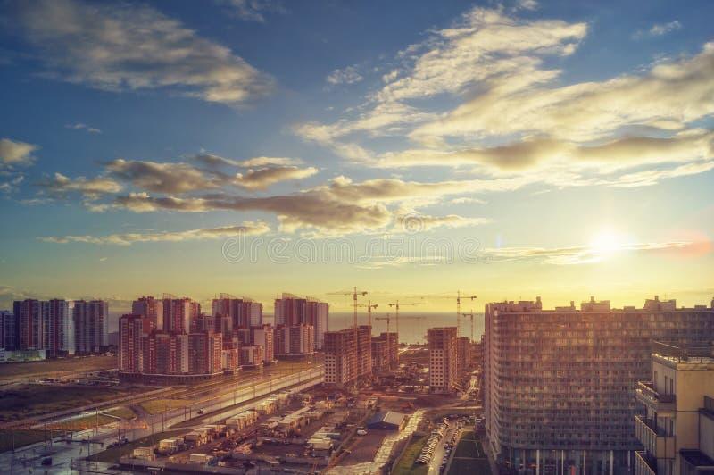 Stad bij zonsondergang De kust van de metropool in de stralen van de avondzon stock foto