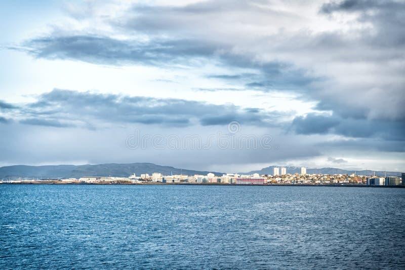 Stad op overzeese kust IJsland Skandinavisch zeegezichtconcept Kalme waterspiegel en stad met hoge moderne gebouwen stock afbeeldingen