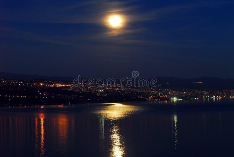 Stad på kusten på natten med månen fotografering för bildbyråer