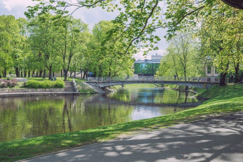 Stad Riga, de Republiek van Letland Stadspark met brug en gebouwen Toeristen het lopen Bomen en waterkanaal 7 mei 2019 Reisfoto royalty-vrije stock fotografie