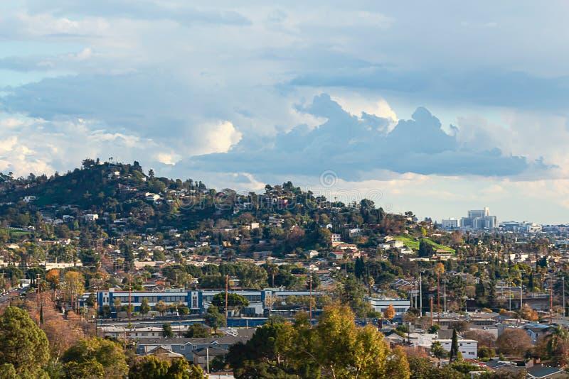 Stad scape met altijdgroene en disiduous bomen met heuvels en bewolkte blauwe hemel en hellingshuizen stock foto's