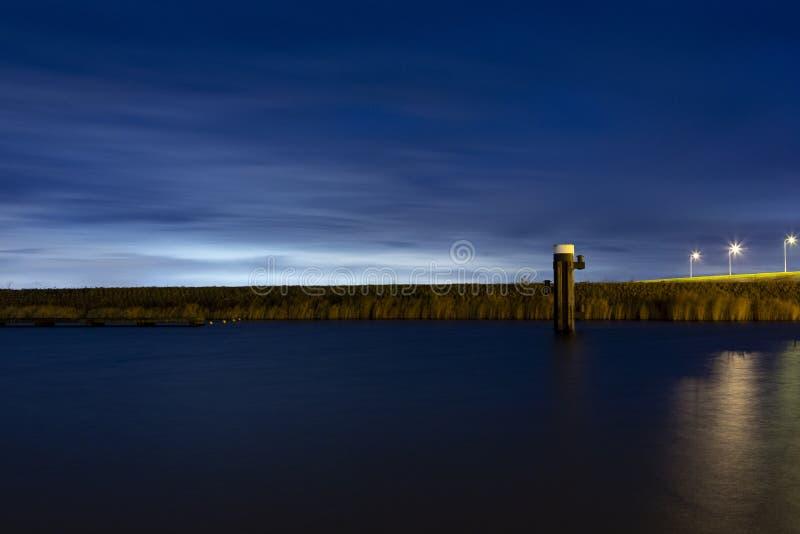 Stad skylight bakom en dyke i en hamn i Bruinisse arkivbild