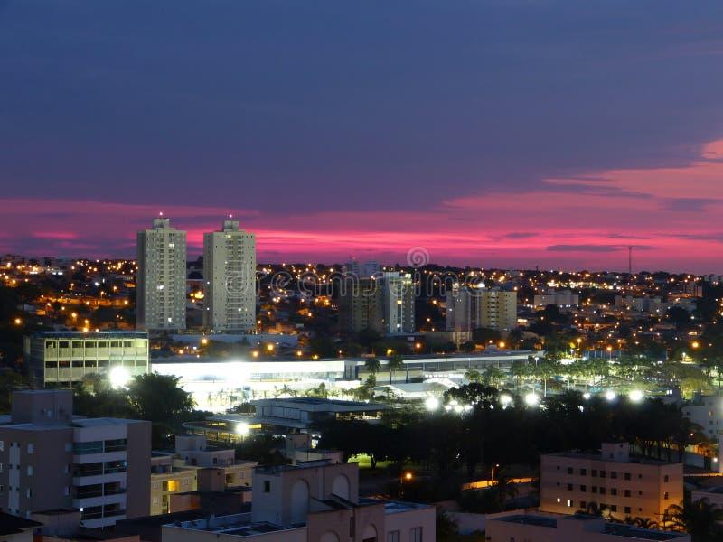 Stad van Uberlandia tijdens schitterende roze zonsondergang Stedelijk landschap van Uberlândia, Minas Gerais, Brazilië stock afbeelding