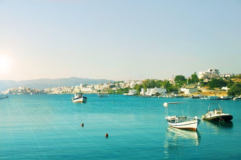 Stad vid medelhavet i turkoslagun, fiskebåtar i turkosvatten på den klara himmelbakgrunden, sommarlandskap arkivbilder