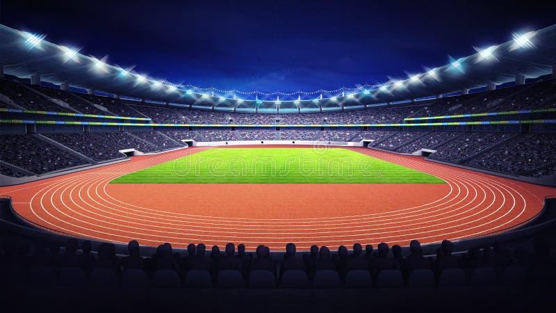 Stade d'athlétisme avec le champ de voie et d'herbe à l'avant la vue de nuit
