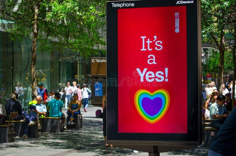 Staden av den understödjande homobröllopet för det Sydney rådet med hjärtaregnbågen på en skärmbildskärm säger ` det ` s ett ja!  arkivbilder
