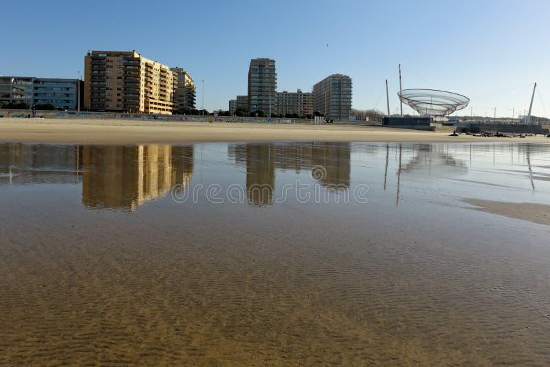 Staden av Matosinhos reflekterade på den våta sanden royaltyfri foto
