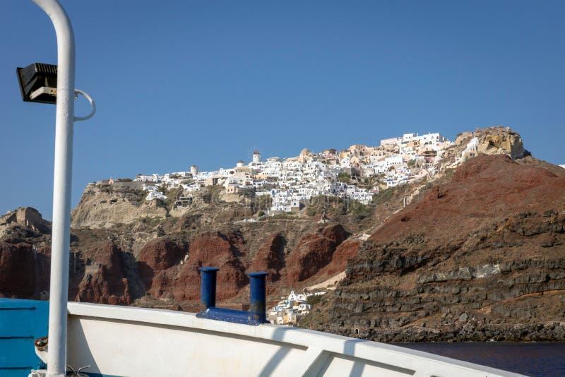 Staden av Oia som ses från vattnet i en fiskebåt arkivbild